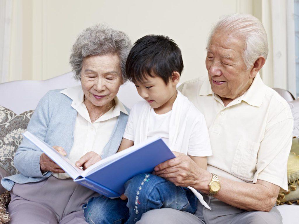 Orchard Ridge Residences | Senior couple reading to grandson