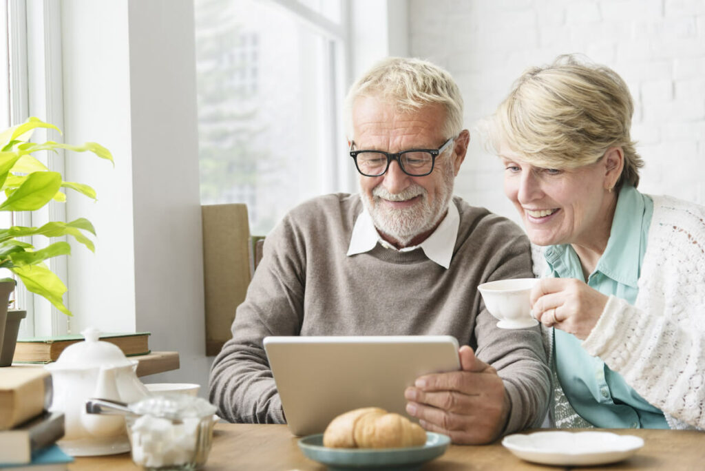 Orchard Ridge Residences | Smiling Couple Looking At An iPad
